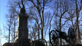 A cannon sits next to the tallest monument on Power's Hill - Rigby's Maryland Battery.
